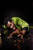 selective focus of drunk african american man lying on floor with shiny confetti on black