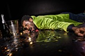 selective focus of drunk african american man lying on floor with shiny confetti near ice bucket and bottle of champagne on black