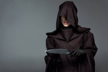 woman in death costume holding knife isolated on grey