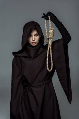 woman in death costume holding hanging noose isolated on grey