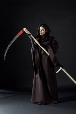 full length view of pensive woman in death costume holding scythe on black
