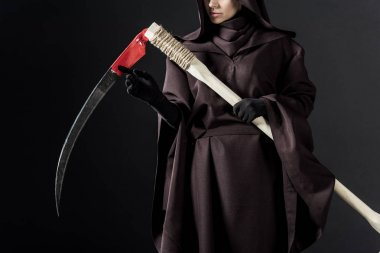 cropped view of woman in death costume holding scythe on black