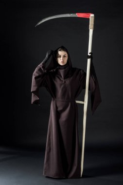 full length view of woman in death costume holding scythe on black