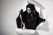 Fotografie Frau im Todeskostüm hält Schlinge in der Hand und steigt aus Loch in Papier