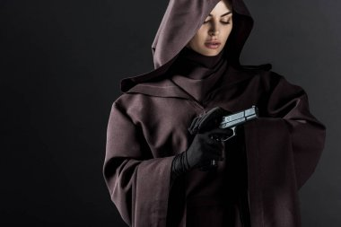 woman in death costume holding gun isolated on black