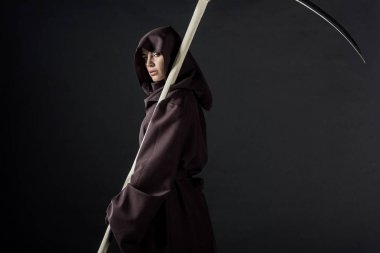 woman in death costume holding scythe and looking at camera isolated on black