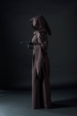 side view of woman in death costume holding gun on black