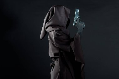 side view of woman in death costume holding gun isolated on black
