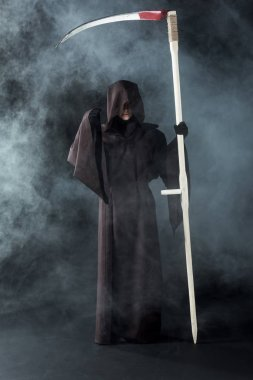 full length view of woman in death costume holding scythe on black with smoke
