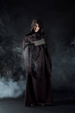 full length view of woman in death costume holding cleaver in smoke on black
