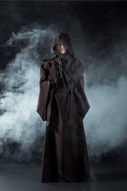 full length view of woman in death costume holding candle in smoke on black