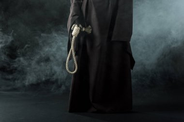 partial view of woman in death costume holding hanging noose in smoke on black