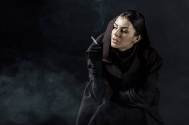 woman in death costume smoking cigarette on black