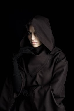pensive woman in death costume looking at camera isolated on black