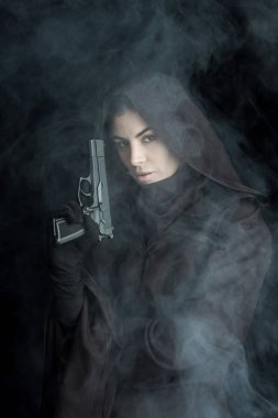woman in death costume holding gun and looking at camera on black