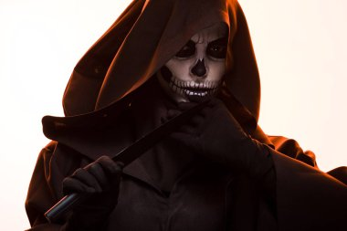serious woman in death costume holding knife on white