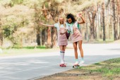Fotografie kompletní pohled na dva usmívající se multikulturní přátele skateboardingu v halových deskách na silnici