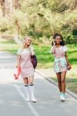 Fotografie v plné délce se dva usměvavé multikulturní přátele s haléřními deskami po silnici a naslouchající hudbě ve sluchátkách