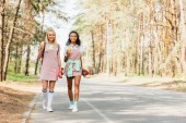 full length view of two multicultural friends with penny boards holding bottles of orange juice while walking on road