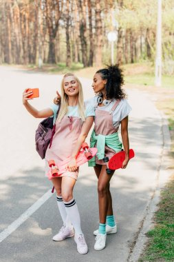 Full length view of two smiling multicultural friends with penny boards taking selfie on road stock vector