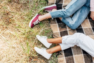top view of two multiethnic friends lying on plaid blanket on ground
