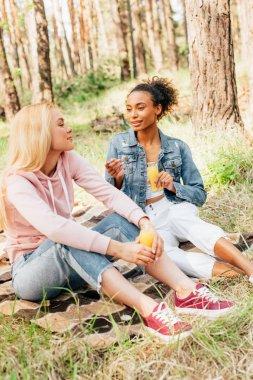 Two multiethnic girls sitting on plaid blanket and holding bottles of orange juice stock vector