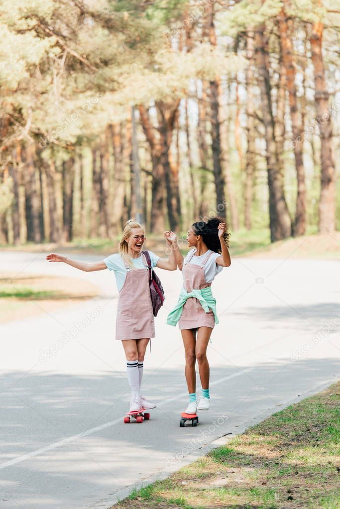 full length view of two smiling multicultural friends holding hands while skateboarding on penny boards on road