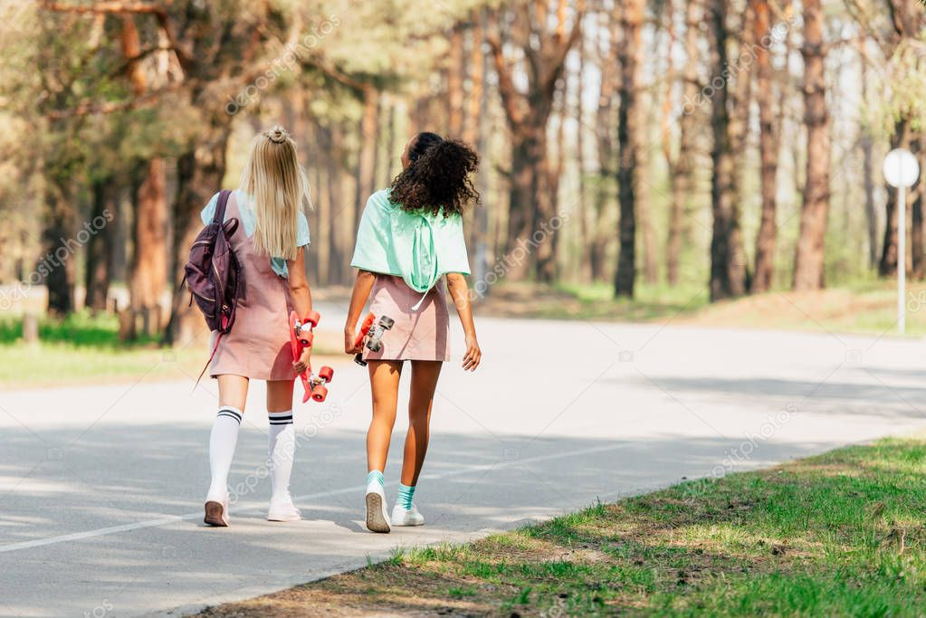back view of two multicultural friends with penny boards walking on road