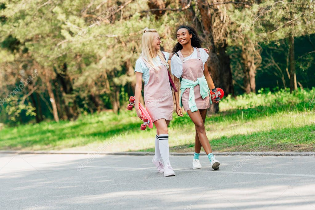 full length view of two multicultural friends with penny boards embracing while walking on road