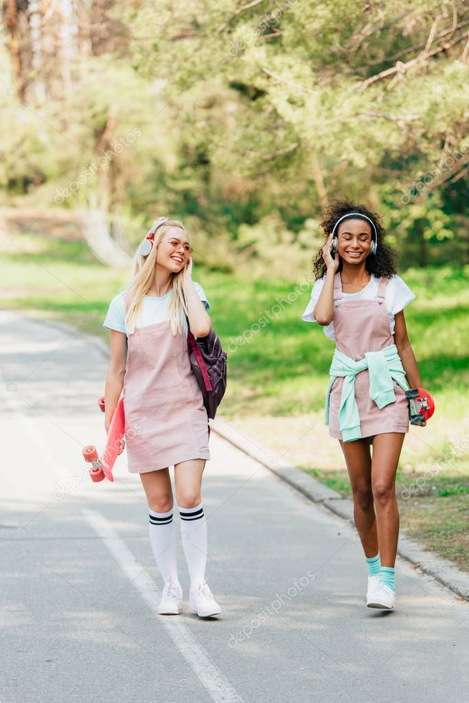 full length view of two smiling multicultural friends with penny boards walking on road and listening music in headphones