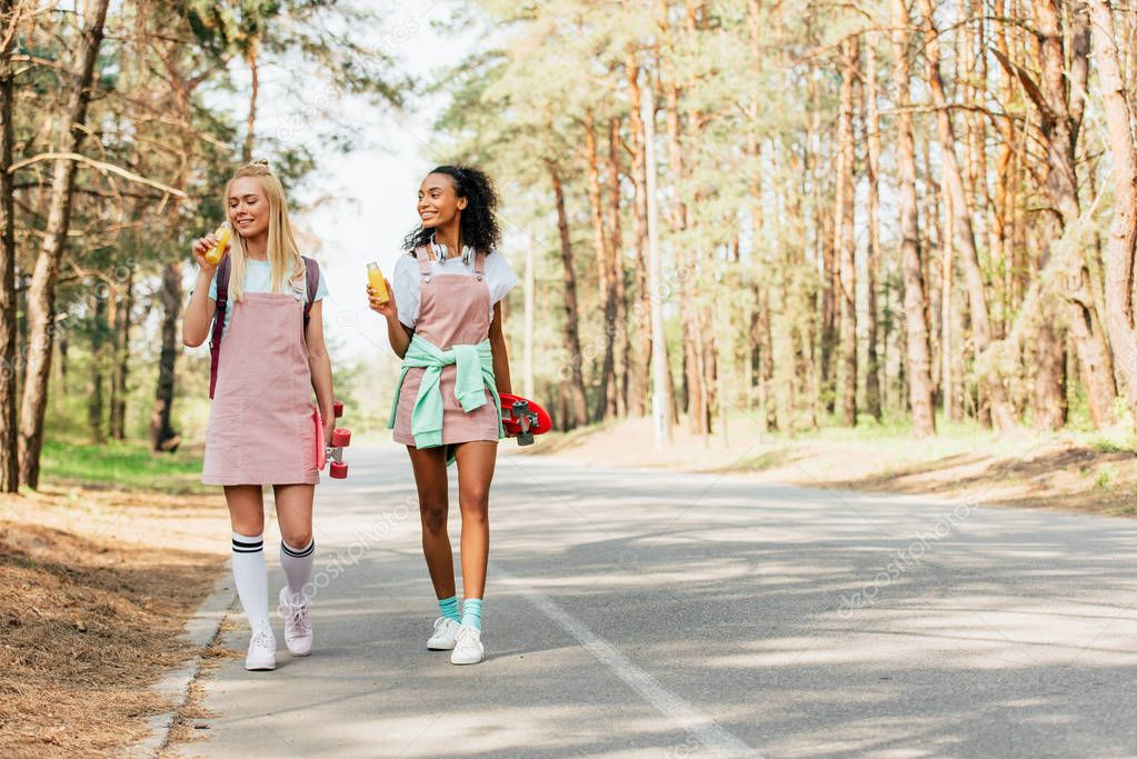 full length view of two multiethnic friends with penny boards holding bottles of orange juice on road