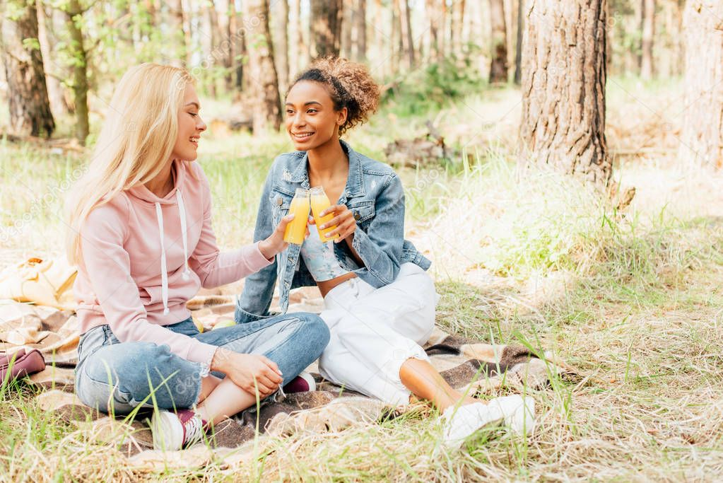 two multiethnic girls sitting on plaid blanket and holding bottles of orange juice