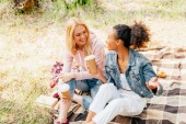 two multiethnic friends sitting on plaid blanket and holding paper cups of coffee