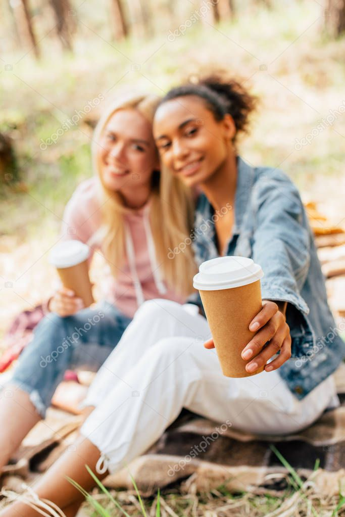 selective focus of two multiethnic friends sitting on plaid blanket and holding paper cups of coffee