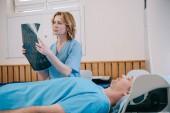 pozorný lékař zkoumáním rentgenové diagnostiky poblíž pacienta ležící na CT skeneru