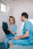 bel medico guardando la diagnosi a raggi X vicino al paziente seduto sul letto scanner mri