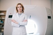 Fotografie attractive confident radiologist standing near mri machine with crossed arms and looking at camera