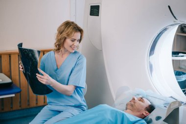 beautiful smiling doctor holding radiology diagnosis and looking at man lying on ct scanner bed