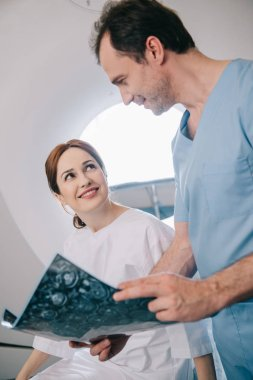 smiling doctor showing digital tablet with x-ray diagnosis to happy patient