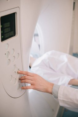 partial view of radiologist operating computed tomography scanner during patients diagnostics