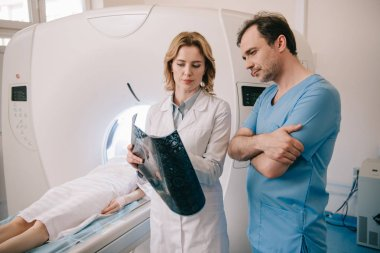 thoughtful doctors looking at x-ray diagnosis during patients diagnostics on ct scanner