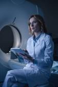 radiologo premuroso in possesso di tablet digitale con diagnosi a raggi-X mentre si è seduti vicino a scanner di tomografia computerizzata e distoltolo