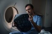 pozorný lékař, který se dívá na diagnostiku tomografie, zatímco sedí poblíž CT skeneru