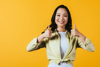 Smiling asian woman showing thumbs up isolated on yellow stock vector