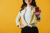 Fotografie oříznutý pohled na brunetu dívku s smartphone s obchodními kurzy, izolované na žluté