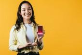 Fotografie šťastná Asijská dívka prezentující smartphone s obchodními kurzy, izolované na žluté