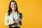 happy asian girl presenting smartphone with marketing analysis, isolated on yellow