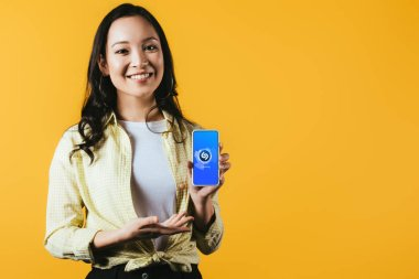 KYIV, UKRAINE - APRIL 16, 2019: smiling asian girl presenting smartphone with shazam app, isolated on yellow