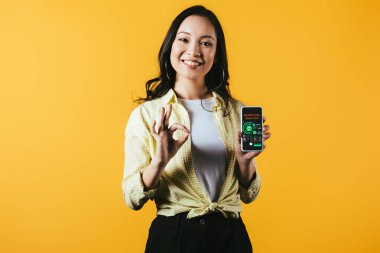 smiling asian girl showing ok sign and smartphone with marketing analysis, isolated on yellow
