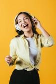 Veselá asijská žena zpívající a naslouchající hudba se sluchátky, izolovaná na žluté
